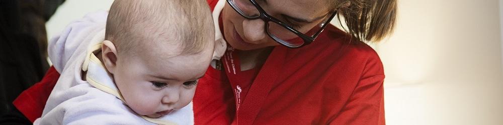 Un'operatrice Sve the Children con uno dei bambini del progetto Fiochi in Ospedale